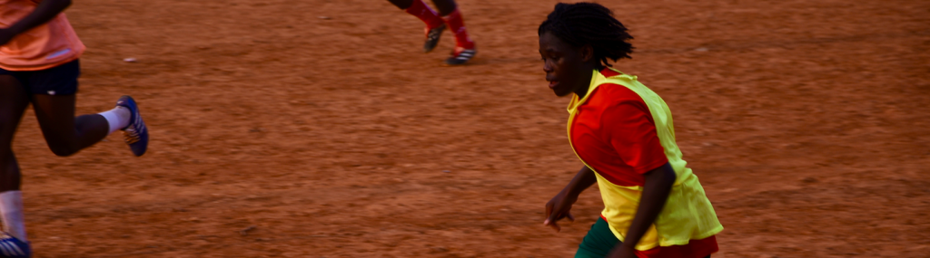 Young woman playing football in Camroon