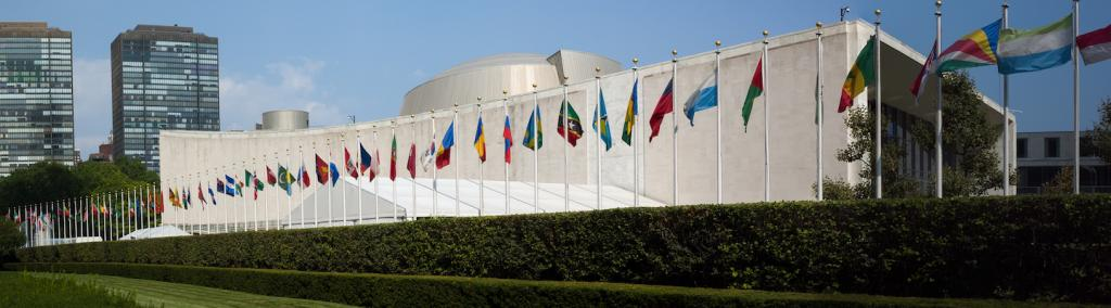 UN General Assembly, world flags flying in front, New York City.