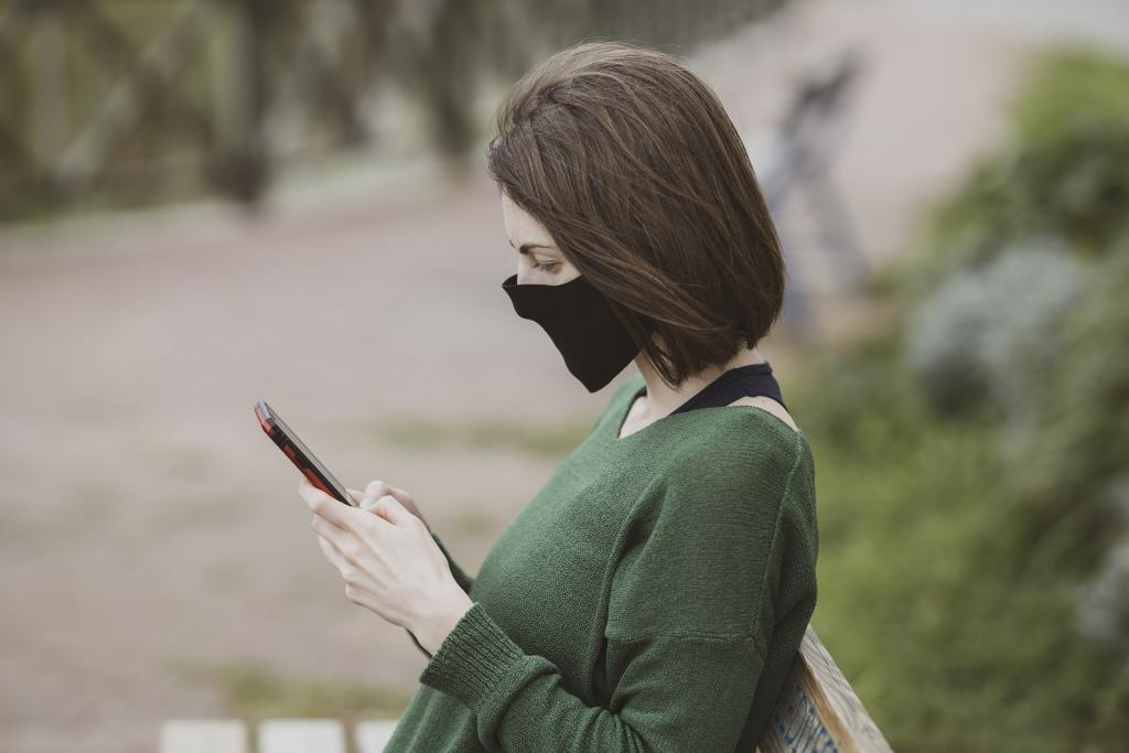 Person with face mask holding a phone