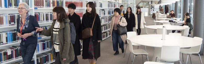Asian visitors guided by a librarian