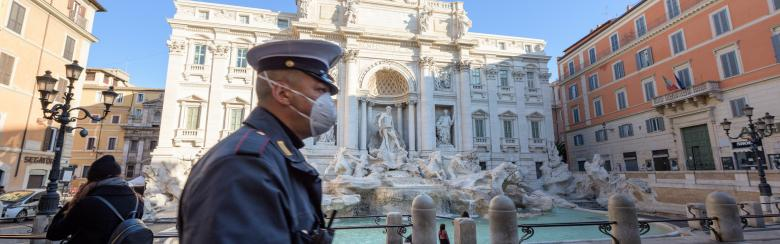 Italian carabineri walks in front of trevi fountain in Rome