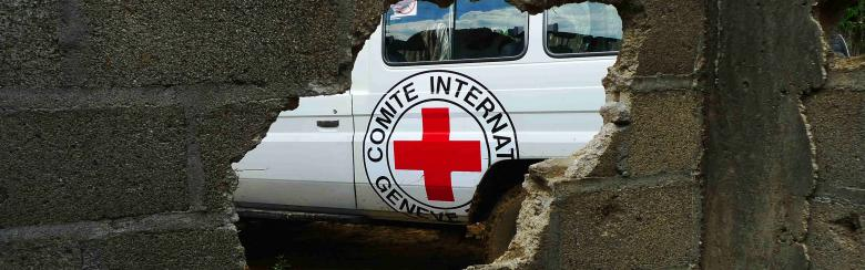 A hole in a wall showing an ICRC truck