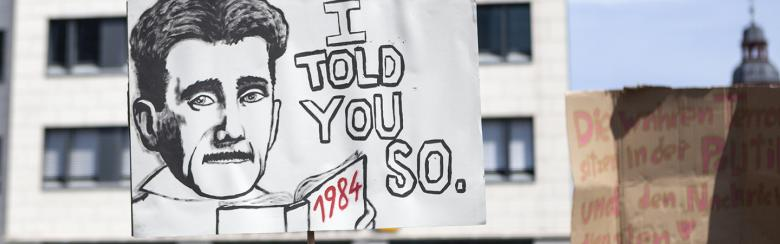 Man holds poster saying I told you so, with 1984 written at the bottom, the book by George Orwell