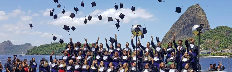 Brazilian students throw their caps in the air after graduating
