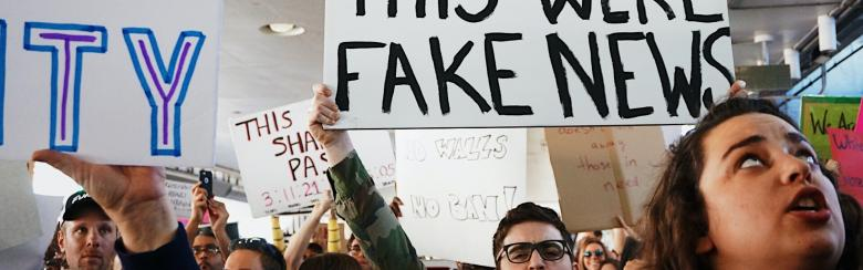 "People holding a sign that reads ""I wish this were fake news"""