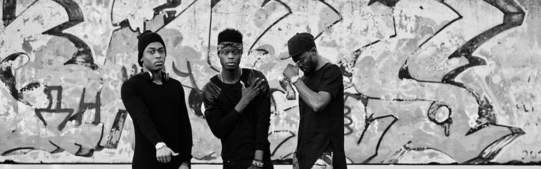 Three rap singers on a roof; background graffiti wall.