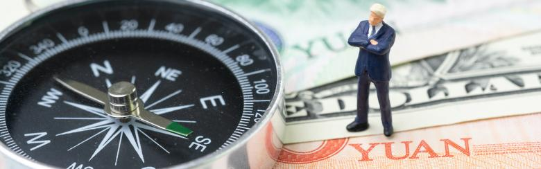 Compass with miniature leader standing on US dollar and China yuan banknotes.