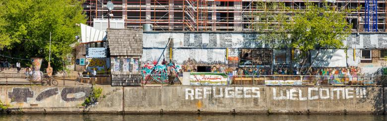 "YAAM night club with sign ""Refugees Welcome!"" along the Spree riverbank in Berlin."